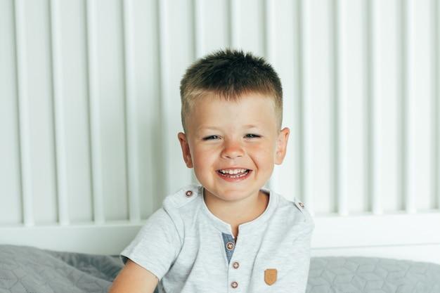 Alter kleiner netter lächelnder und habender spaßjunge auf einem bett im schlafzimmer.