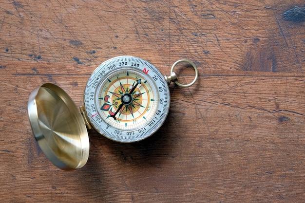 Alter kompass im geöffneten messinggehäuse auf braunem hölzernem hintergrund des vintagen, der zur nordansicht-draufsicht nahe oben gezeigt wird