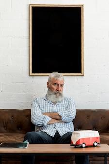 Alter kunde, der auf sofa am friseursalon sitzt