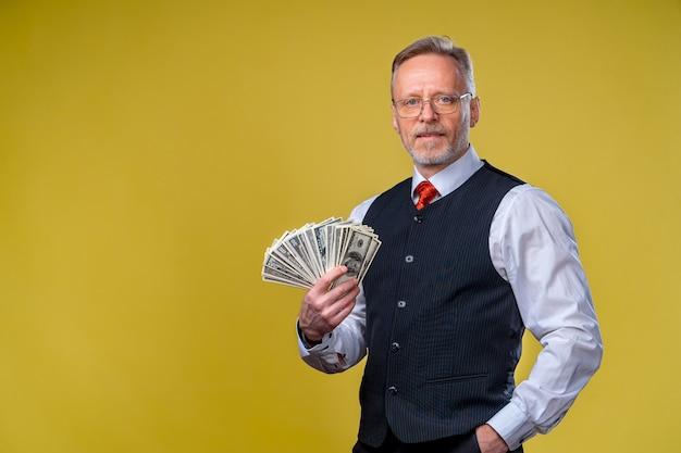 Alter lächelnder grauhaariger mann mit brille, der dollar-fan in der hand hält. fröhliches lächeln im gesicht. viel geldscheine. menschliche emotionen und mimik.