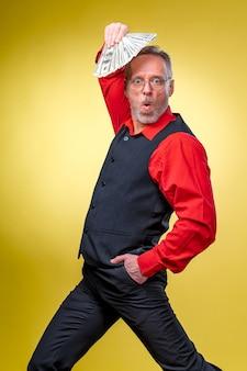 Alter lächelnder grauhaariger mann mit brille, der einen dollar-fan über dem kopf in tanzender pose hält. menschliche emotionen und mimik