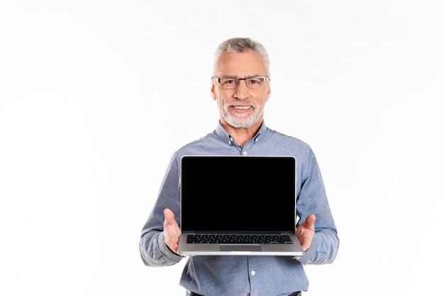 Alter lächelnder mann, der laptop mit leerem bildschirm lokalisiert zeigt