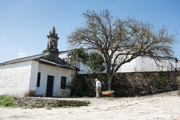 Alter landwirt, der schwer während des klaren sonnigen tages im frühjahr nahe der kapelle in spanien arbeitet