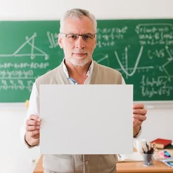 Alter lehrer, der klares blatt papier zeigt