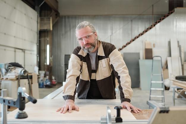 Alter männlicher arbeiter in arbeitskleidung und schutzbrille, der sie beim bücken über die werkbank mit festem brett oder werkstück ansieht