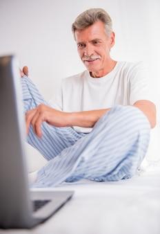 Alter mann benutzt laptop beim sitzen im weißen bett.