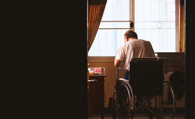 Alter mann, der alleine in einem rollstuhl am haus sitzt
