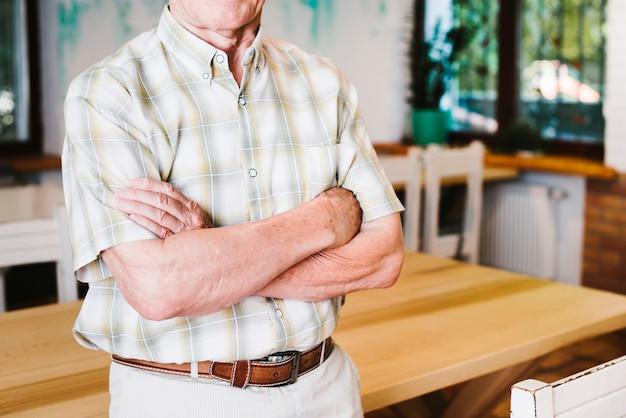 Alter mann, der arme kreuzend steht