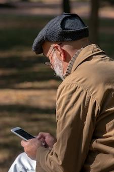 Alter mann, der auf der bank mit einem smartphone sitzt