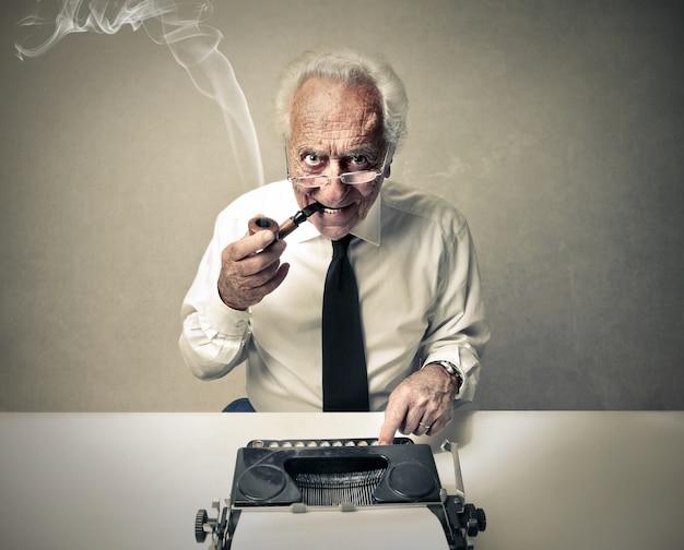 Alter mann, der auf einer schreibmaschine schreibt