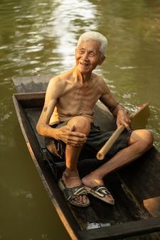 Alter mann, der boot im kokosnussbauernhof verwendet