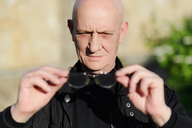 Alter mann, der brille in seiner hand hält