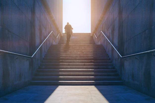 Alter mann, der die granittreppe hinauf zum sonnenlicht klettert. gehender mann zum ziel. konzept, um die ziele zu erreichen. gelegenheitstreppe, weg zum scheitern oder zum erfolg.
