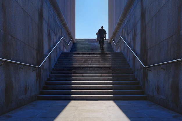 Alter mann, der die granittreppe klettert. gehender mann zum ziel. konzept, um die ziele zu erreichen. gelegenheitstreppe, weg zum scheitern oder zum erfolg.