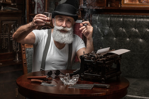 Alter mann, der drinnen eine zigarre raucht. mafia-konzept. stilvoller mann in seinem schrank. bärtiger mann.