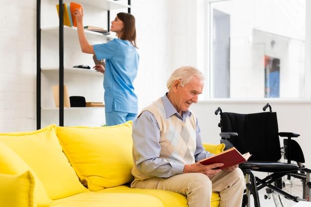 Alter mann, der ein buch beim sitzen auf gelbem sofa liest