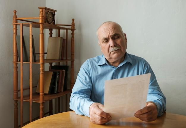 Alter mann, der ein papierdokument oder einen brief liest