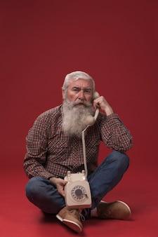 Alter mann, der ein telefon hält