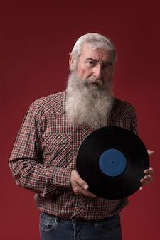 Alter mann, der eine vinylscheibe hält
