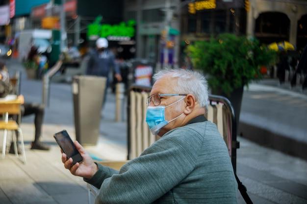Alter mann, der handy auf new york city im tragen der gesichtsmaske verwendet
