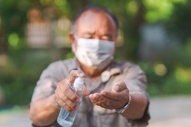 Alter mann, der ihre hände mit sprühendem antiseptischem alkoholgel säubert hygienekonzept