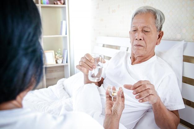 Alter mann, der im bett sitzt und seine pillen nimmt