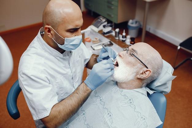 Alter mann, der im büro des zahnarztes sitzt