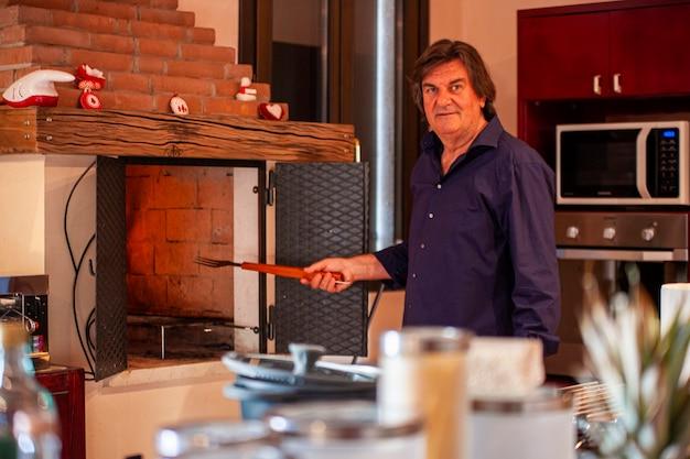 Alter mann, der in der küche seines hauses kocht