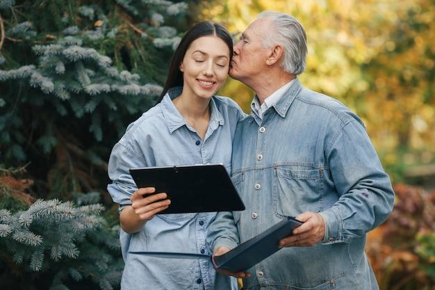 Alter mann, der in einem parkhintergrund mit seiner enkelin steht
