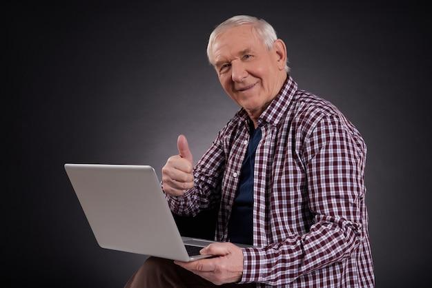 Alter mann, der mit dem laptop getrennt auf schwarzem sitzt.