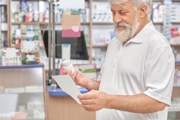 Alter mann, der pillenflasche und -verordnung betrachtet.