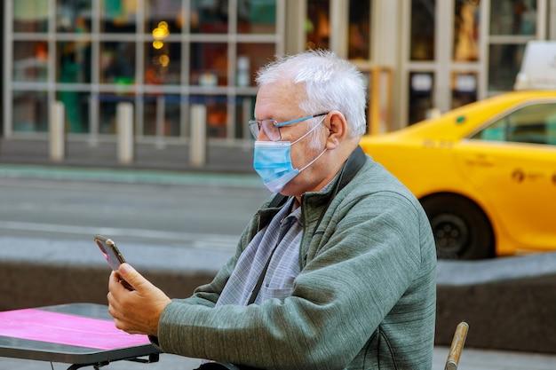 Alter mann, der sein handy benutzt, während er die straßenmaske entlang geht, um sich während der pandemie in new york vor dem coronavirus zu schützen