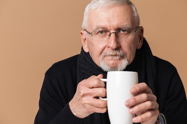 Alter mann, der teeporträt trinkt