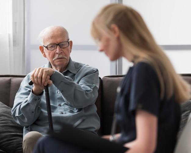 Alter mann, der von krankenschwester konsultiert wird