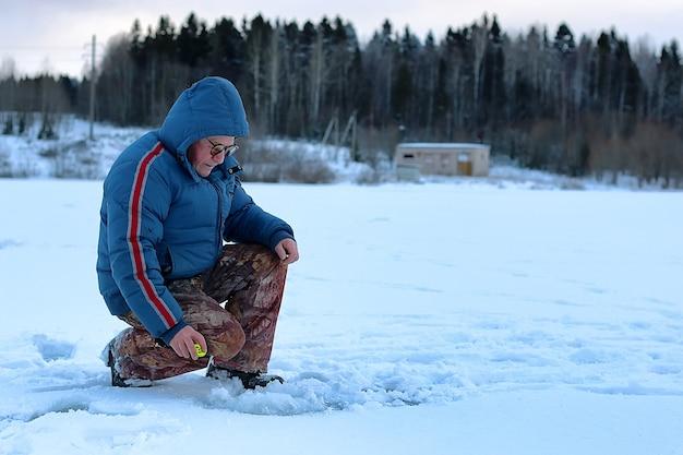 Alter mann der wintersaison, der auf einem see fischt