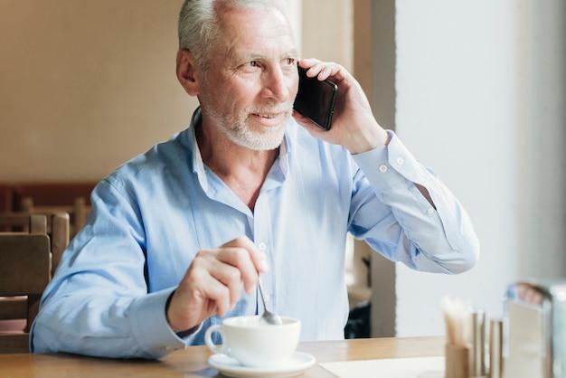 Alter mann des mittleren schusses, der am telefon spricht