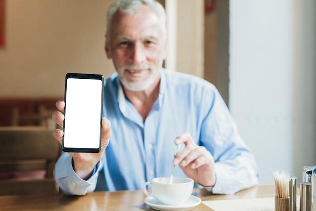 Alter mann des mittleren schusses, der einen smartphone hält