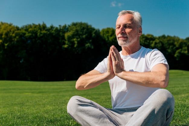 Alter mann des mittleren schusses, der in der natur meditiert