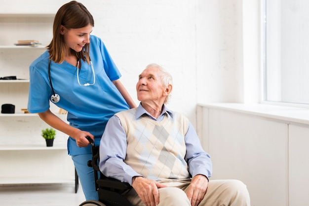 Alter mann des mittleren schusses im rollstuhl, der krankenschwester betrachtet