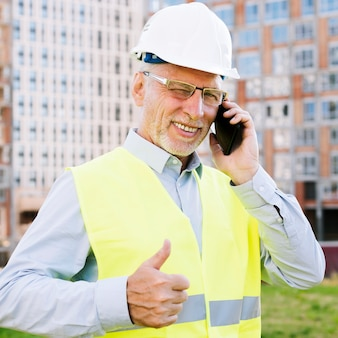 Alter mann des mittleren schusses mit dem telefon, das zustimmung zeigt
