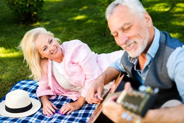Alter mann des smiley, der gitarre am picknick spielt