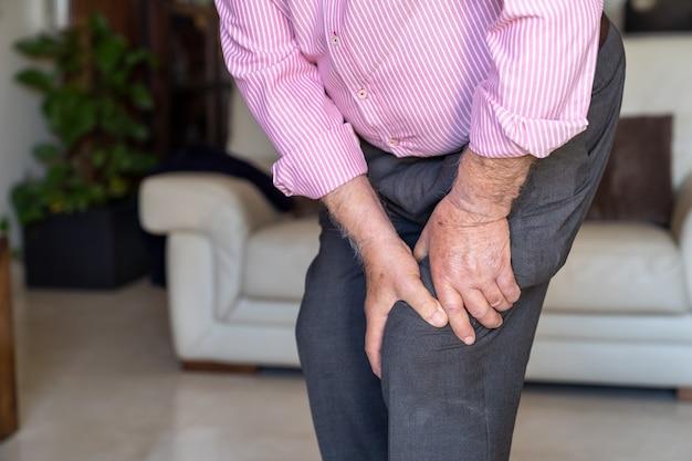 Alter mann fühlte schmerzen auf seinem knie und berührte es