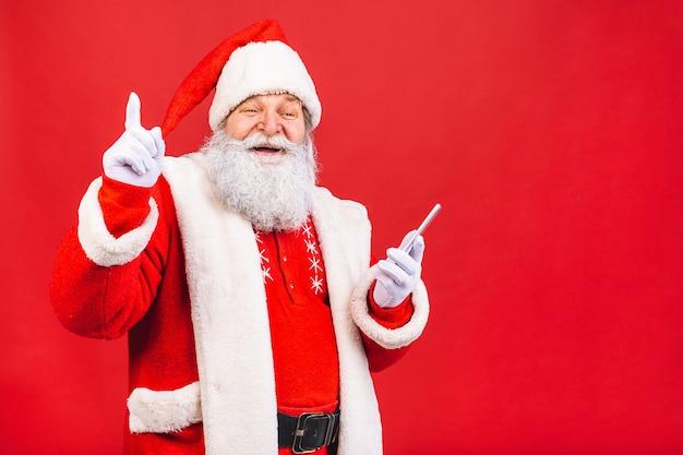 Alter mann im weihnachtsmannkostüm, das auf einem handy lokalisiert auf rotem hintergrund hält