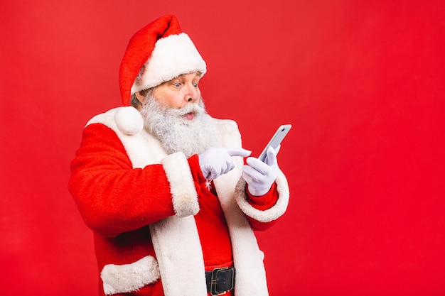 Alter mann im weihnachtsmannkostüm, das auf einem mobiltelefon lokalisiert auf rot hält