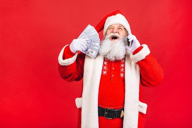 Alter mann im weihnachtsmannkostüm, das auf einem mobiltelefon lokalisiert auf rotem hintergrund spricht