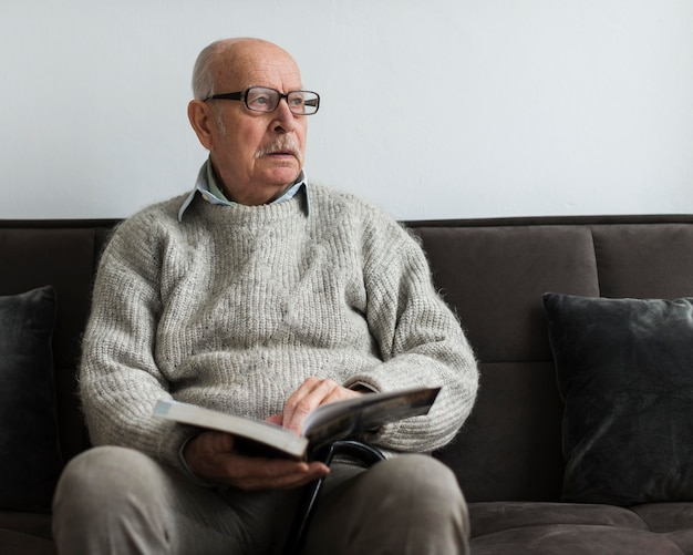 Alter mann in einem pflegeheim, der ein buch liest