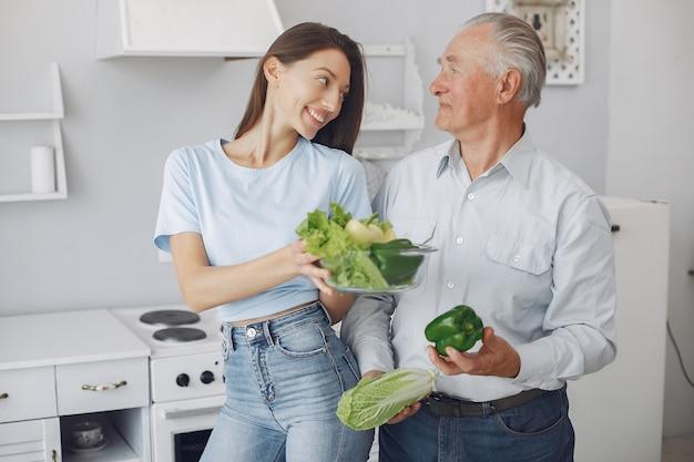 Alter mann in einer küche mit junger enkelin