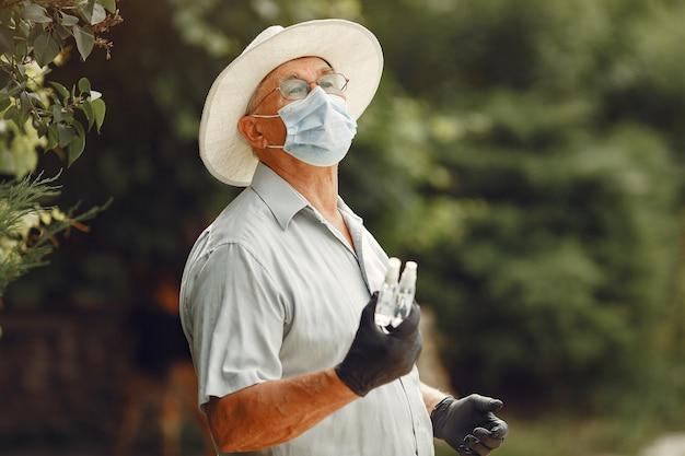 Alter mann in einer medizinischen maske. mann im park. coronavirus-thema.