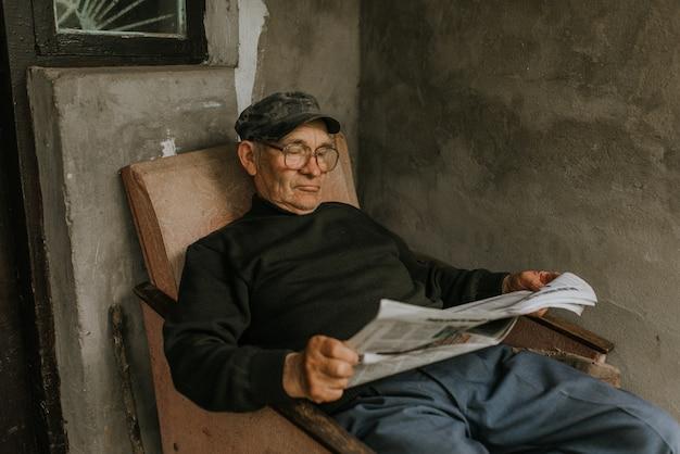 Alter mann in gläsern mit grauem haar, das eine zeitung liest