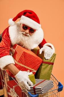 Alter mann in santa kostüm mit geschenkboxen im warenkorb